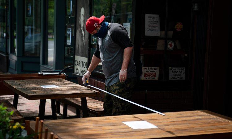 Un ristoratore che misura il distanziamento fra tavoli