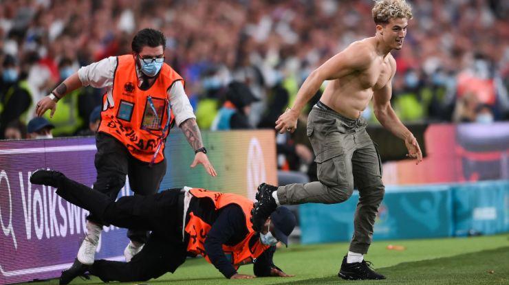 Gli steward rincorrono il tifoso in campo